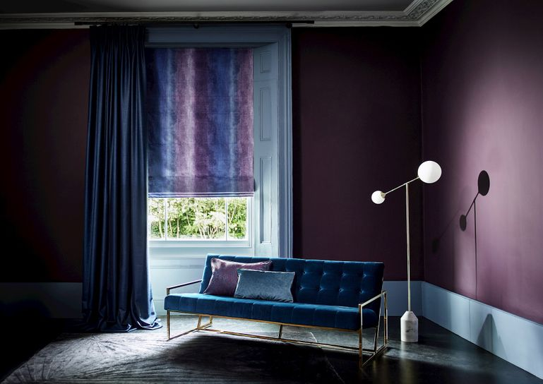 Living room with blue velvet sofa, purple ombre Roman blind and navy blue curtains
