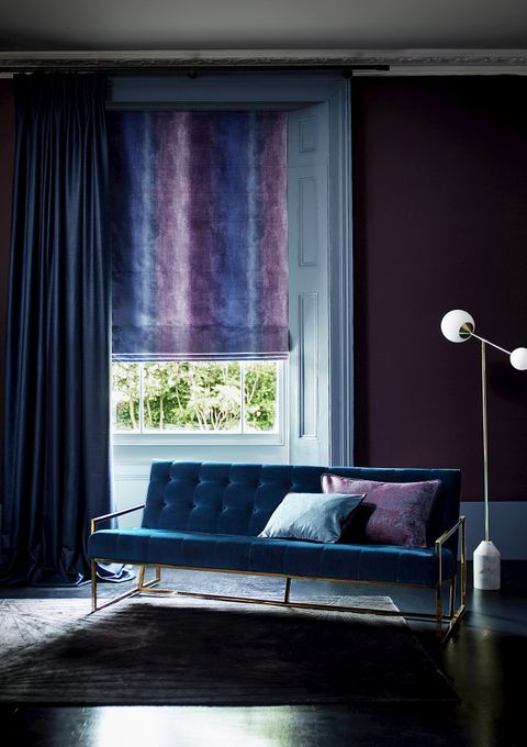 Close up of living room window with ombre velvet Roman blind and blue curtains