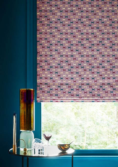 Close up detail of window with pink geometric Roman blind and dark teal painted walls