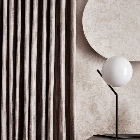Close up detail of silver curtains and glass globe table lamp