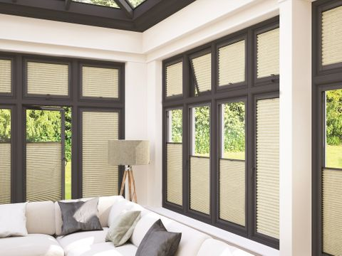 Modern conservatory with dark frame windows dressed with cream thermals blinds
