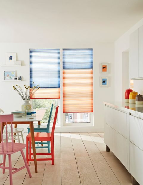 Colourful kitchen with full length windows with orange and blue thermal blinds