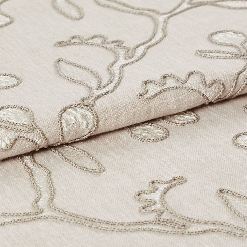 Folded fabric in a neutral colour with a repeating leaf and stem pattern in a slightly darker style