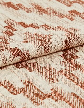 Cream coloured base fabric which is patterned in a repeating tribal design in dark orange