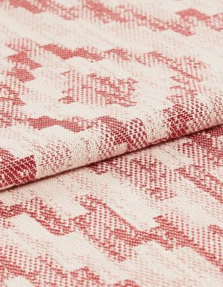 Cream base colour material that is folded and has a repeating tribal pattern that is styled in pink