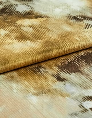 A folded piece of fabric decorated with aurora ember in dusty gold, brown and white
