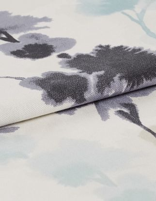 White fabric that is decorated with flowers in an ink blot style