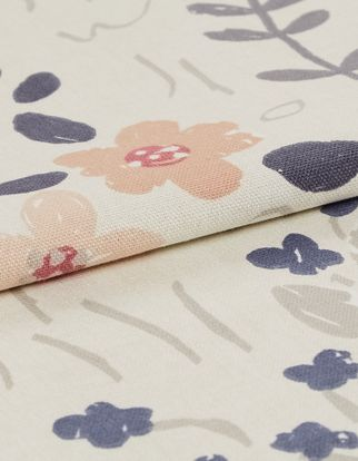 Cream coloured fabric with flowers in a variety of shapes and colours that pattern the material
