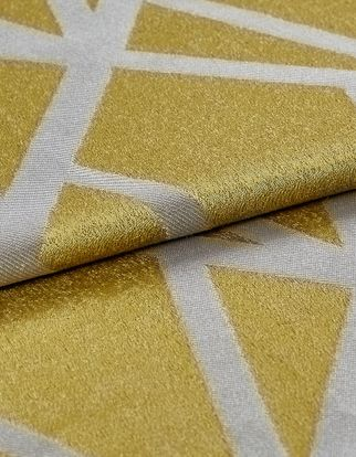 Shiny gold coloured fabric which is folded over with a repeating geometric pattern in bright white