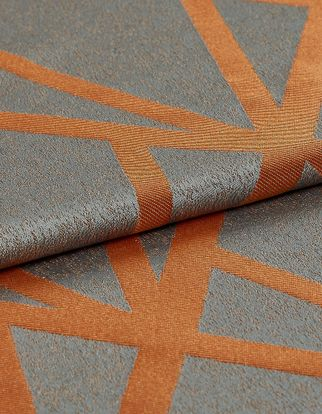 The material is dark grey with a slight shine to it and layered with geometric designs that criss cross in thick lines of orange