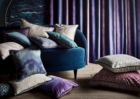 Cushions in varying shades of blue, purple and beige are piled on a blue arm chair with purple curtains in the background