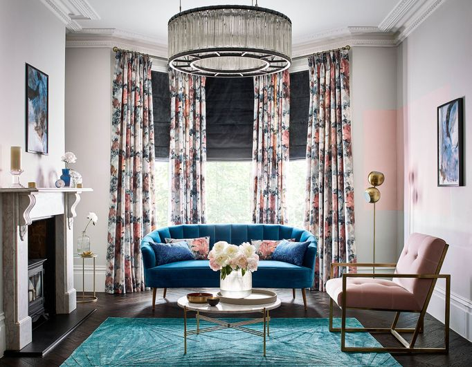 Living room windows dressed with dark grey roman blinds behind floral velvet curtains