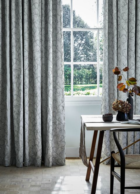 Close up detail of light sage green  curtains featuring delicate embroidery in a dining room