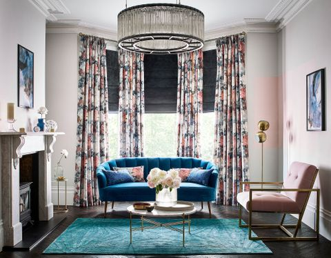 Living room windows dressed with black roman blinds behind floral velvet curtains