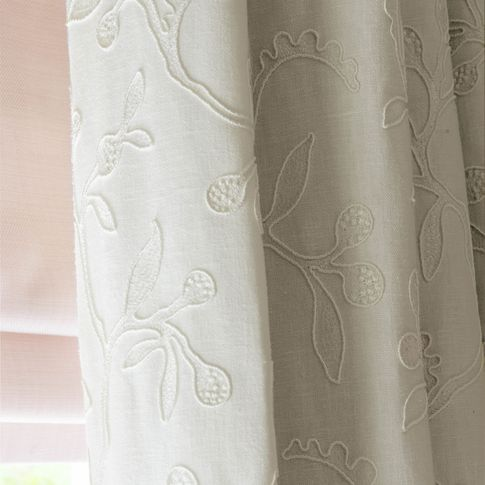 close up cream curtains featuring delicate embroidery hanging on bedroom window