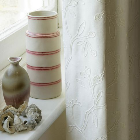 Close up of bedroom window dressed with cream curtains featuring delicate embroidery