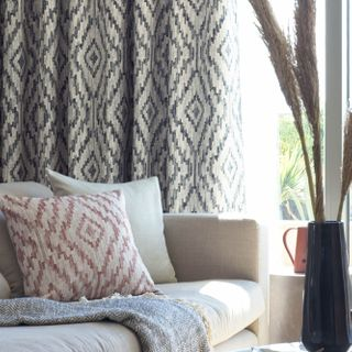 Close up detail of sofa with geometric print curtains