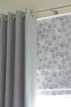 Close up of Bailey Cloudy curtains and Honesty Frost Roman blinds in bedroom