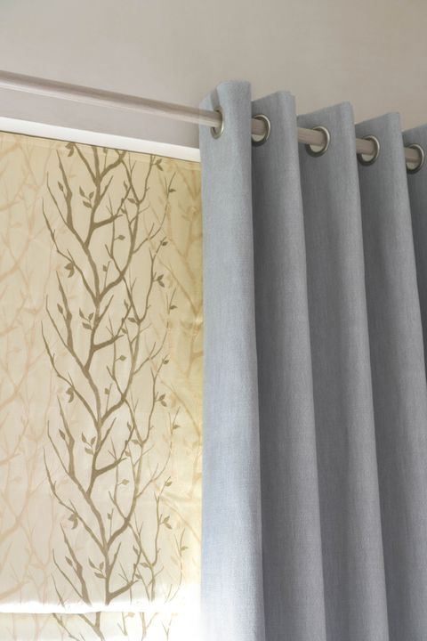 Close up of Bailey Cloudy eyelet  curtains and Pyrus Cream Roman blinds in bedroom