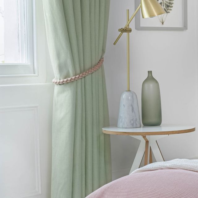 Close up of bailey neo mint curtains with plait tie-back in bedroom