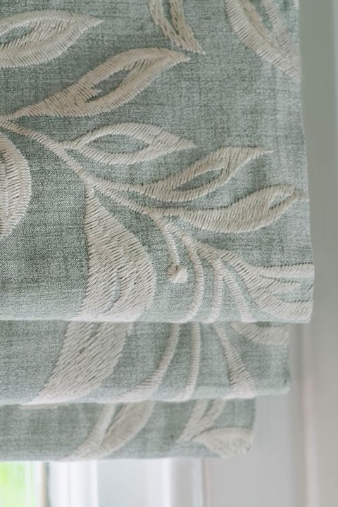 Close up of light blue Roman blinds featuring white embroidery in a bedroom