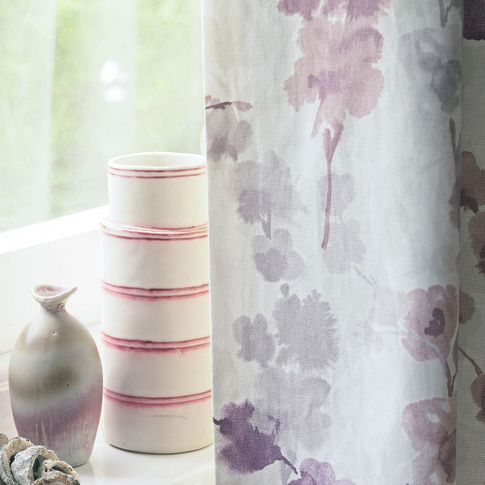 Close up detail of vases on windowsill and purple floral curtain