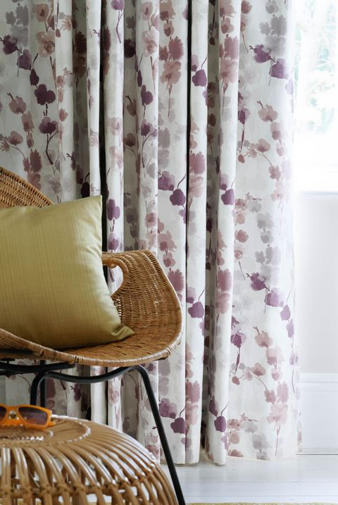 Close up detail of purple floral curtains and wicker chair