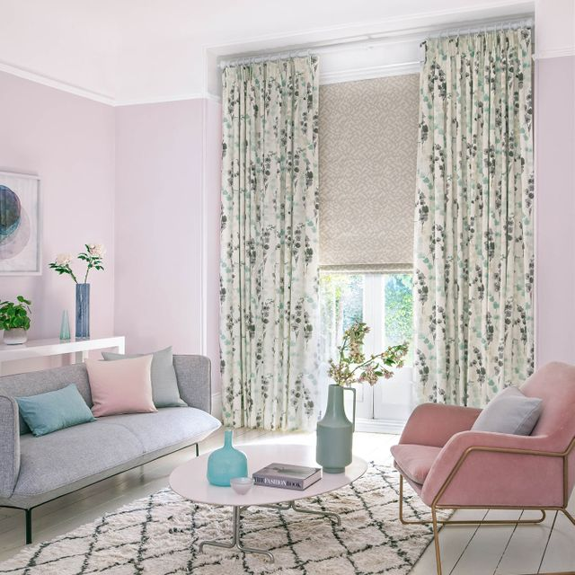 Light and fresh living room with lilac floral curtains and a lavender geometric print Roman blind