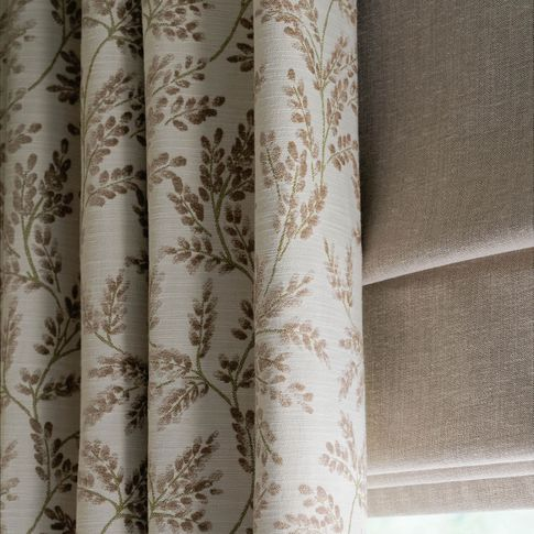 Close up detail of Delizia Taupe curtains and Lindora Linen Roman blinds at a single windowdining room
