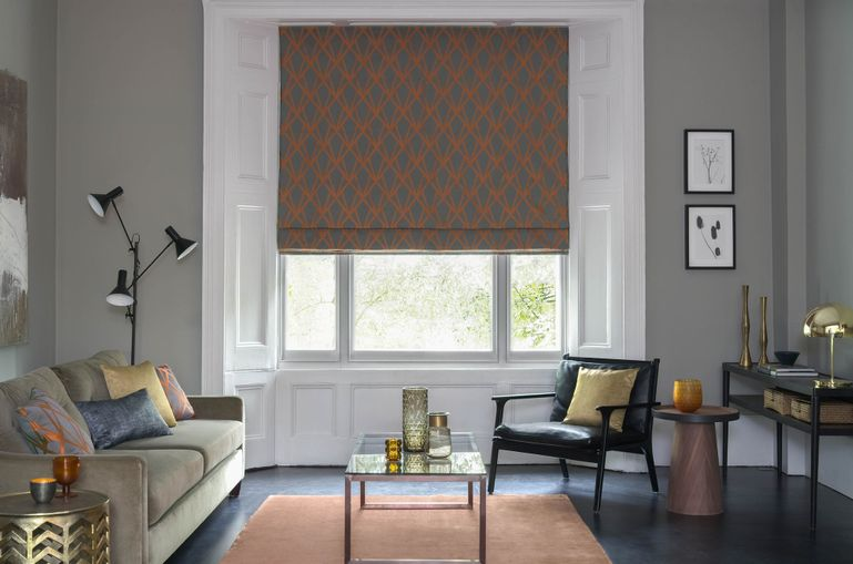 Dimension Ember geometrical patterned Romans in grey and copper in a grey living room