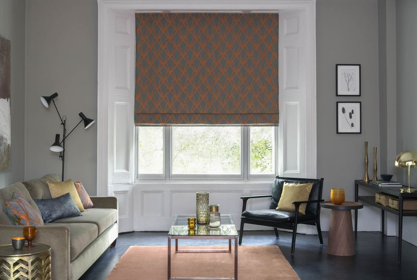 Dimension Ember geometrical patterned Roman blinds in grey and copper in a grey living room