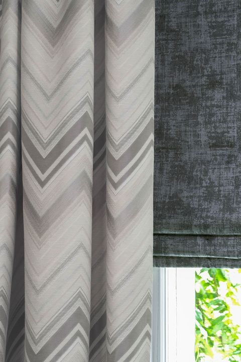 Close up of grey pattern curtains and black roman blinds in living room