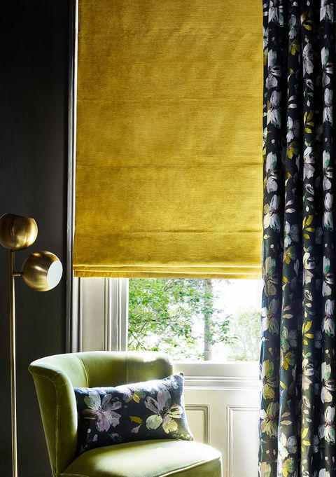 Close up detail of living room window with floral curtains and yellow velvet Roman blind