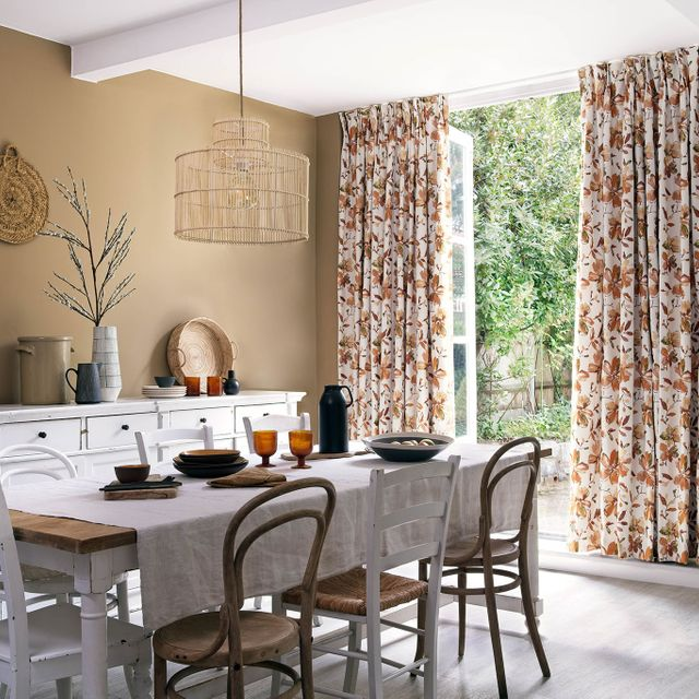 Rustic dining room with french doors opening onto the garden. Floral curtains at the window