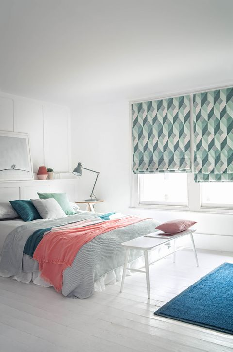 A white Roman blind features a double bed that has cushions and throws on it. There is a window behind the bed partially covered by a roman blind in shades of forest green, mint green and grey.