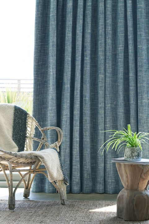 Close up of wicker chair in front of window with Haddie Ocean curtains