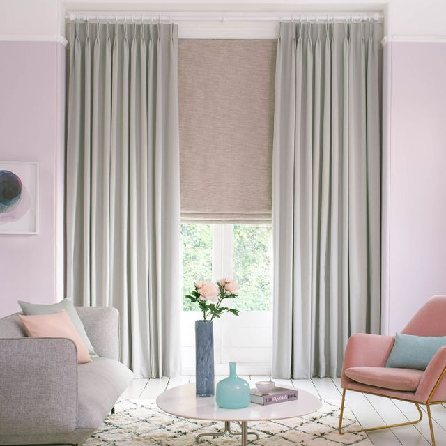 Huxley Dove Grey curtains with a Haddie Chalk Pink roman blind in soft pink living room. Two chairs are featured in this image along with a table that has vases and a book