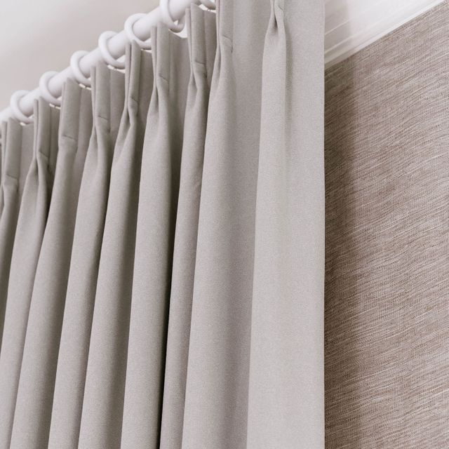 Close up of double pinch pleat header type on white curtain pole