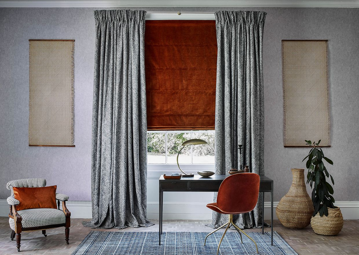 A dark desk and bright orange chair sit in front of a window with a orange blind. The blind is combined with grey detailed curtains. There are also two fabric wall hangings on either side of the window.