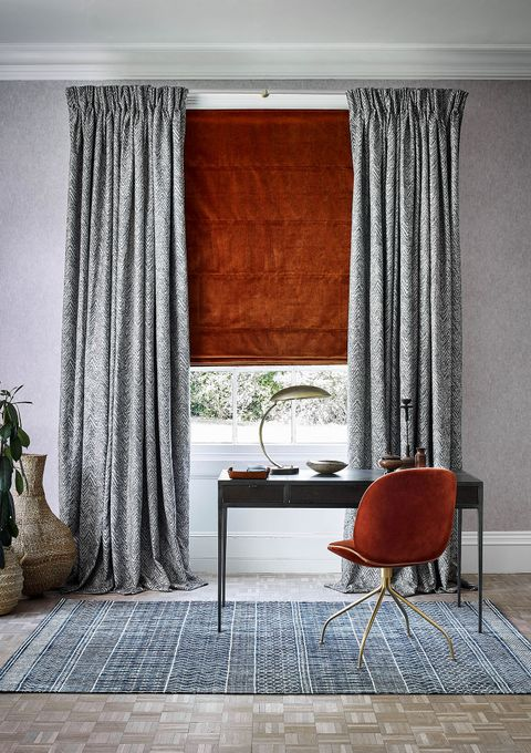 Home office with geometric print curtains and a velvet Roman blind