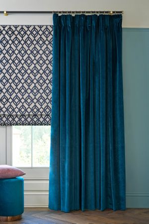 Velvet curtains in a deep blue shade hang over a Roman blind featuring a white and blue diamond design. The blue shade is repeated with the addition of blue cushions on a stool in front of the window