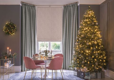 Muse Pearl roman blinds under daze silver curtains in a dining room setting with christmas tree