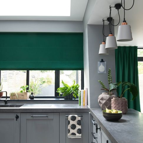 Green curtains and roman blinds in kitchen