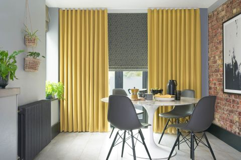 Mustard curtains and grey printed roman blinds in dining room