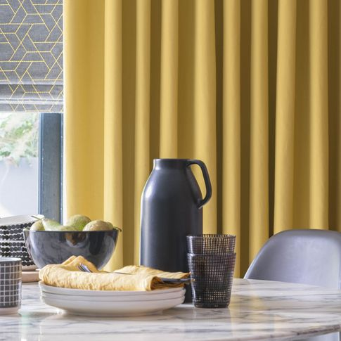 Close up of  Mustard curtains and grey printed roman blinds in kitchen