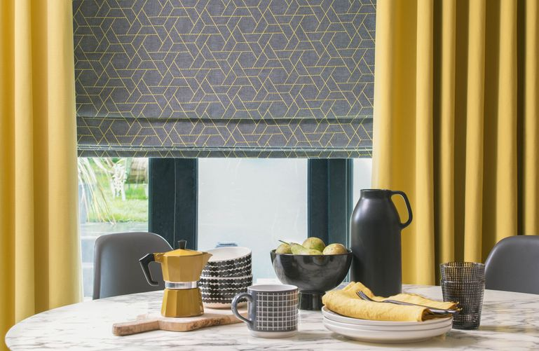 A table set for breakfast sits in front of a window featuring bright yellow blinds and a grey Roman blind that has a geometrical yellow design on it. The yellow of the curtains is echoed in the choice of yellow kitchen accessories