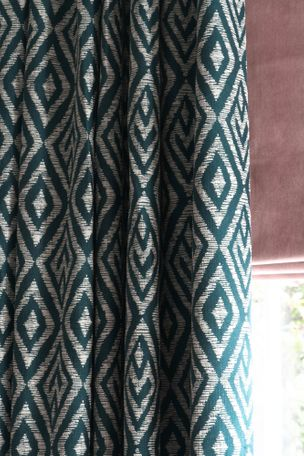 Close up of window dressed with a pink Roman blind and green geometric print curtains