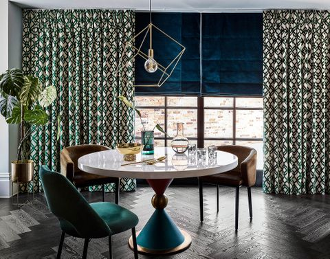 Art deco inspired dining room with velvet geometric print curtains in white and forest green over a deep blue Roman blind.