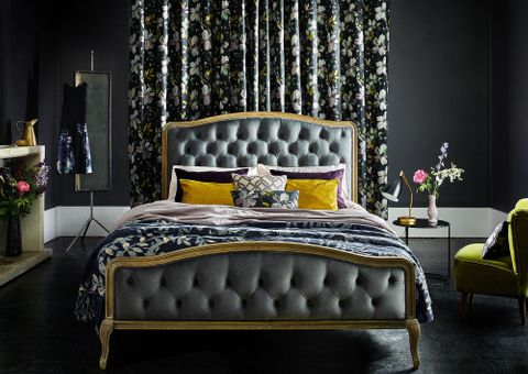 Dark painted bedroom with floral curtains behind a double bed