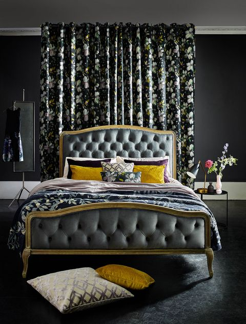 Dark painted bedroom with floral curtains behind a double bed with mustard, purple and pink pillows